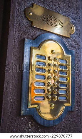 Old italian wooden door with a metal intercom - stock photo