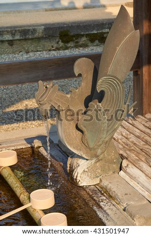Old Japanese temple fountain with mythical creature guarding the water. - stock photo