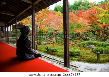 Old Japanese woman in Enkoji temple enjoys Autumn colorful Japanese garden in Kyoto, Japan. - stock photo