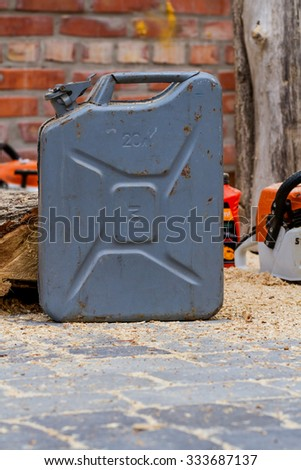 Old jerrycan with gasoline near the chainsaw and logs - stock photo