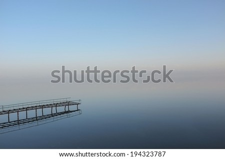 Old jetty on Lake Issyk Kul in the summer evening. Amazing abstract sunset seascape. Minimalistic misty mystic scenery. - stock photo