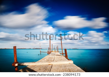 Old jetty walkway pier on the blue sea - stock photo