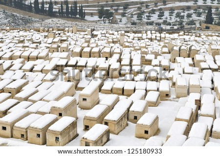 Old Jewish cemetery in mt. of olives covered with rare snow - stock photo