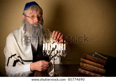 Old jewish man with beard lighting candles for hannukah - stock photo