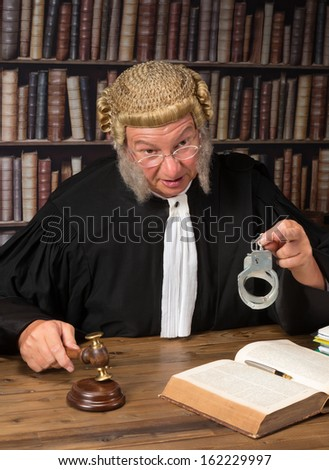 Old judge with authentic wig in courtroom holding handcuffs - stock photo