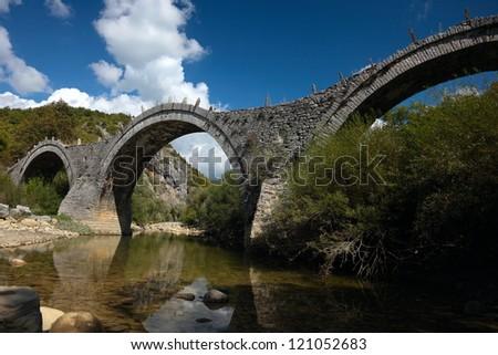 Old Kalogeriko triple arched stone bridge on Vikos canyon, Zagorohoria, Greece - stock photo
