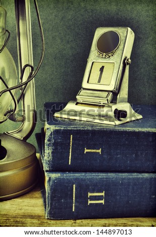 old kerosene lamp and a stack of books - stock photo
