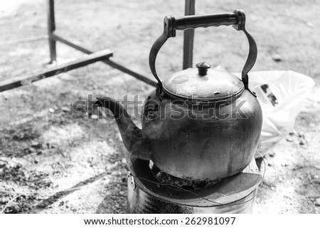 old kettle for boiling water on charcoal stove - stock photo