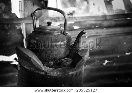 Old kettle for boiling water on stove In kitchen the countryside ,Black and white tone. - stock photo