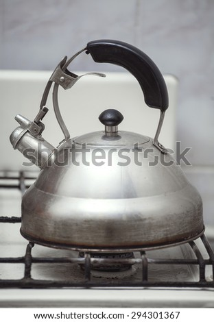 old kettle on the old gas stove - stock photo