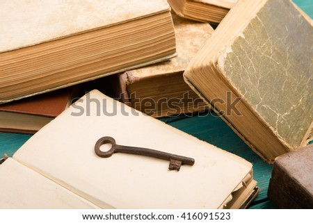 Old key and stack of antique books - stock photo