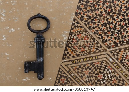 old key on ancient background - arabic ornaments - stock photo