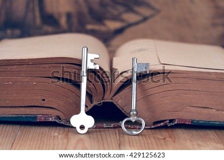 old key on old book wit wood background. - stock photo