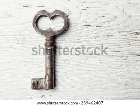 Old key on wooden table - stock photo