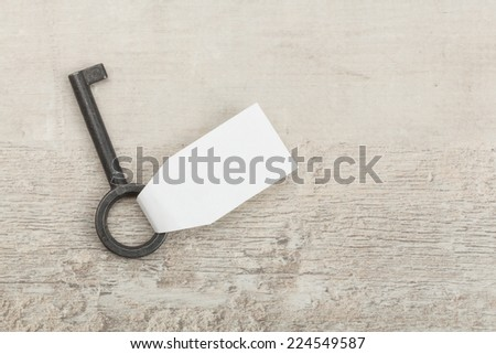 Old key with a heart on white wooden background  - stock photo