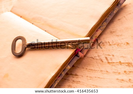 Old key with open blank notebook on wooden table - stock photo