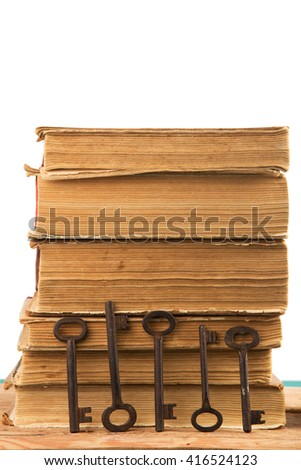 Old keys and stack of antique books isolated on white background - stock photo