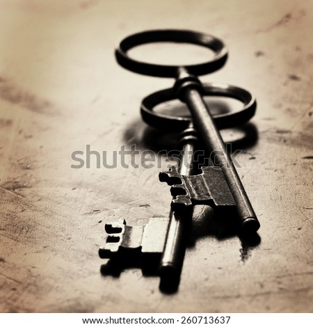 Old keys laying on top of worn wood - stock photo