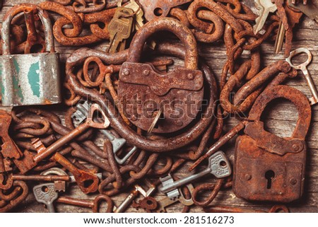 old keys locks over vintage wooden table - stock photo
