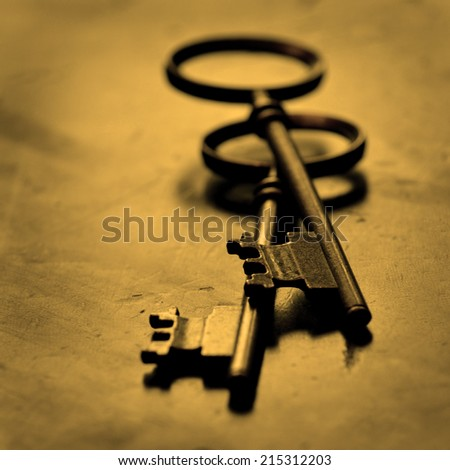Old keys lying on top of worn wood - stock photo