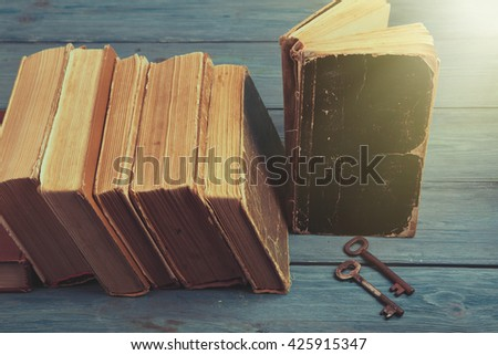 Old keys on a old book and stack of antique books on blue wooden background - stock photo