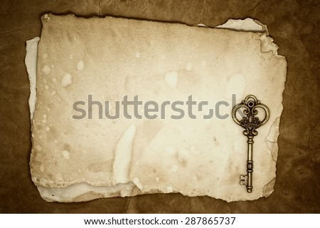 Old keys on old paper with copy space for use as background - stock photo