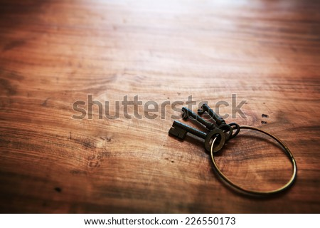Old keys with an brass ring, on old rustic wood surface. Shallow depth of field. - stock photo