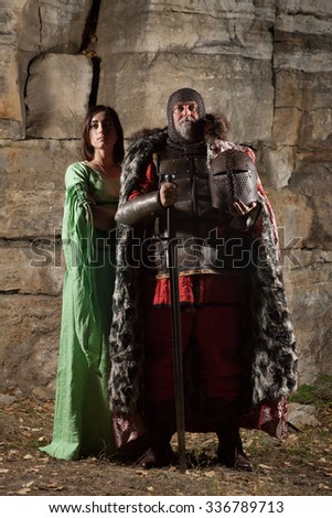 Old King with the sword is leaving his princess. Rocks on the background. - stock photo
