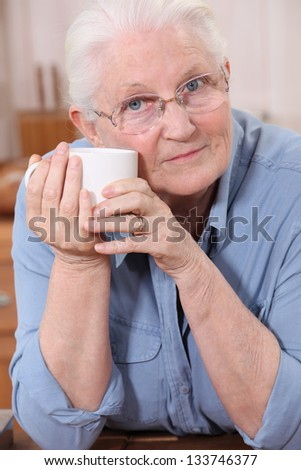 Old lady drinking from mug - stock photo