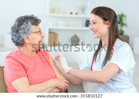 Old lady having an injection - stock photo