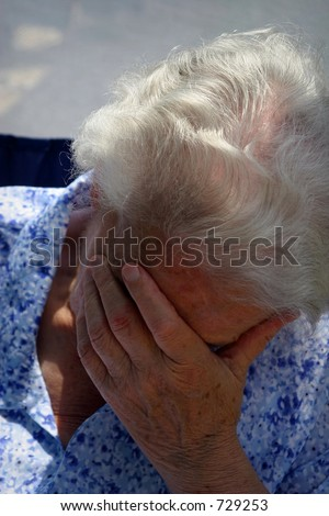 old lady holding her head and crying - stock photo