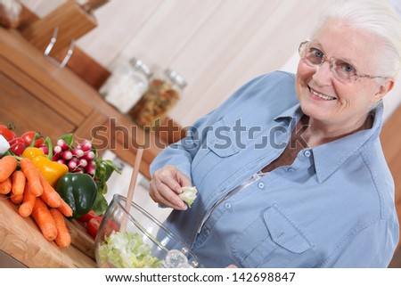 Old lady in kitchen preparing salad - stock photo