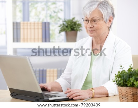Old lady sitting at desk at home, using laptop.? - stock photo