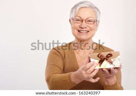 Old lady smiling, holding fancy present box. - stock photo