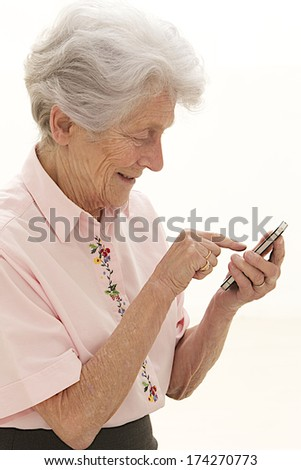 Old lady texting someone using her cell phone  - stock photo