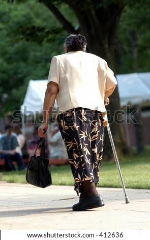 Old lady walking up a  hill with  cane - stock photo