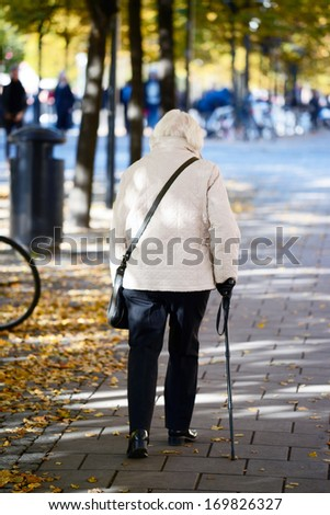 Old lady walking with stick - stock photo