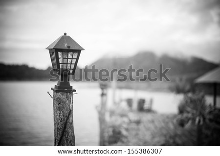 Old lamp on pillar on beautiful view for background, black and white - stock photo