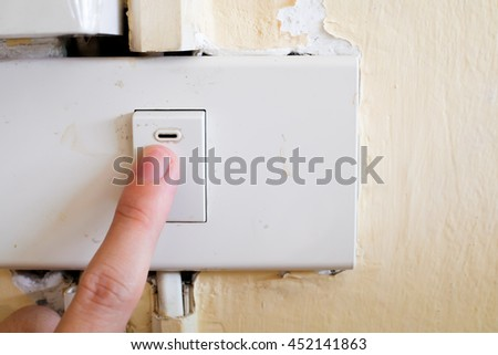 Old lamp switch with pushing hand  - stock photo