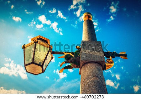 Old lamppost with small horse statue over blue sky in Saint Petersburg, Russia. - stock photo