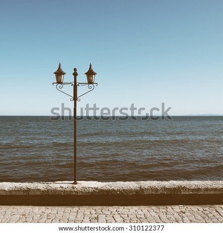 Old lantern on sea background in retro style - stock photo