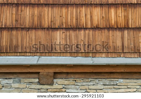Old larch wood shingle wall with stone foundation - stock photo