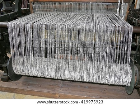 old last century loom for the production of the fabrics in the textile industry with the black and white color woolen threads for the production of woolen blankets - stock photo