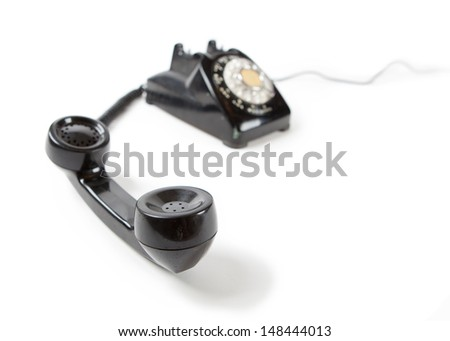 Old Late 60s - 70s style black telephone with rotary dial. Isolated on white. Hand set off the hook and unattended.   - stock photo