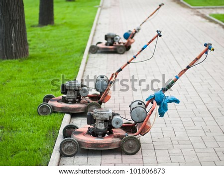 Old lawnmowers on the street in the city - stock photo