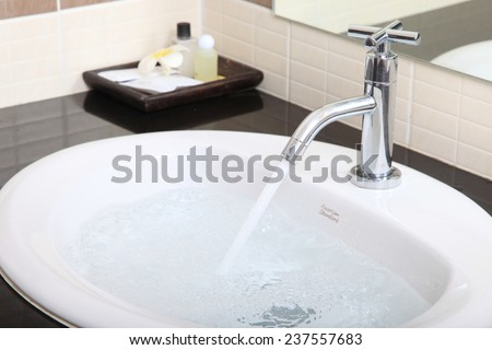 Old leaky faucet gushes on a blurred background. - stock photo
