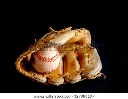 Old leather baseball mitt and used ball on black background. Great image for Major League baseball playoffs or championship in October. Baseball is called the Great American Pastime.  Copy space - stock photo