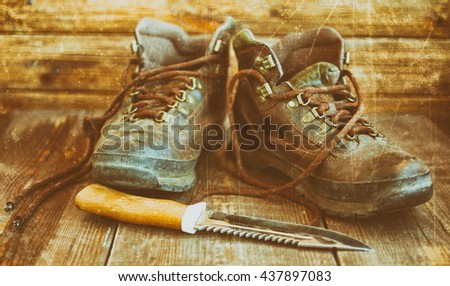 Old leather boots and hunting knife. Boots on a wooden background. Vintage toning - stock photo
