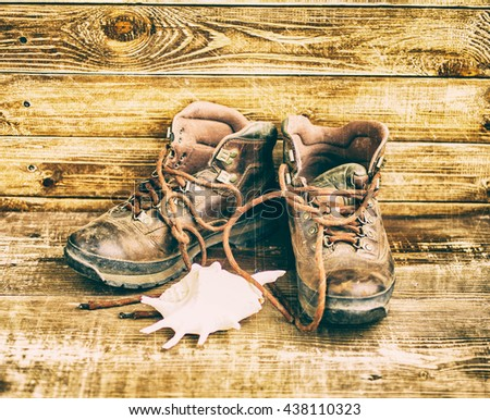 Old leather boots. Boots on a wooden background. Vintage toning Wind of wanderings - stock photo