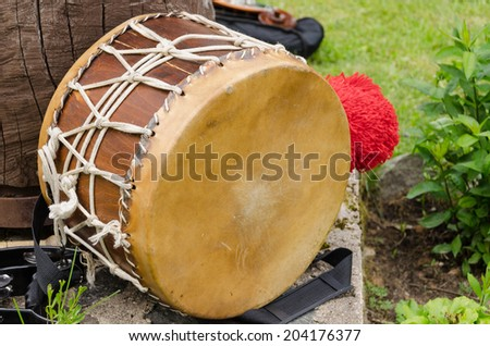 old leather drum with African motifs outdoor  - stock photo